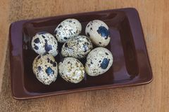 Quail eggs in plate On the old wood table. Background stock image