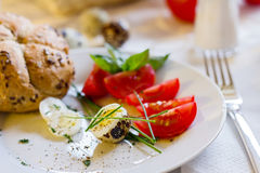 Quail eggs on a plate. With tomatoes and roll Stock Photo
