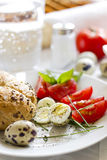 Quail eggs on a plate. Quail eggs with tomatoes, roll and basil Stock Photography
