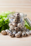 Quail eggs in the pot with hinged lid and greens Royalty Free Stock Image