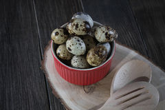 Quail eggs in red pot on dark background. Quail eggs in red pot and kitchen tools. Healthy  food concept on wooden table Royalty Free Stock Photography