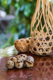 Quail eggs in round bamboo basket on a wooden table Stock Photo