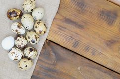 Quail eggs on sacking on a dark brown wooden surface, top view,. Empty place for text, recipe stock image