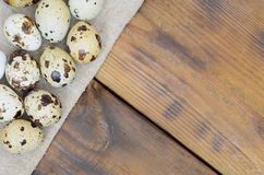 Quail eggs on sacking on a dark brown wooden surface, top view,. Empty place for text, recipe royalty free stock photo