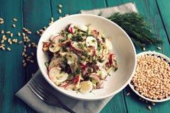 Quail eggs salad in a white bowl. European cuisine. Quail eggs salad in the white bowl. Healthy lunch. European cuisine. Close up. Radish, cucumber, quail eggs Royalty Free Stock Images