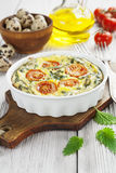 Quail eggs scrambled with nettle and cherry tomatoes Stock Images