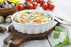 Quail eggs scrambled with nettle and cherry tomatoes Royalty Free Stock Image