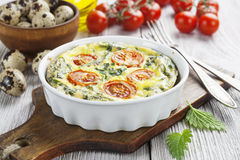 Quail eggs scrambled with nettle and cherry tomatoes Royalty Free Stock Photos