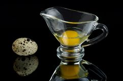 Quail eggs in the shell and in a glass gravy boat on a black mirror surface.  stock photos
