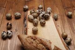 Quail eggs. And some bread on a vintage wooden trencher stock image