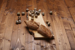 Quail eggs. And some bread on a vintage wooden trencher royalty free stock photography