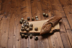 Quail eggs. And some bread on a vintage wooden trencher Royalty Free Stock Images