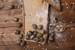 Quail eggs. And some bread on a vintage wooden trencher royalty free stock image