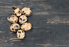 Quail eggs. Some raw quail eggs on a wooden background, top view stock image