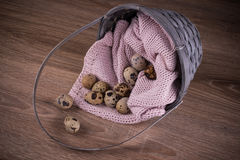 Quail eggs spilling out of basket with pink textile on wooden  background Stock Photo