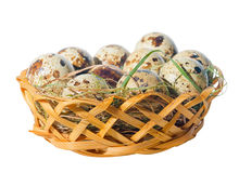 Quail eggs with straw in basket isolated on white background, Royalty Free Stock Photos