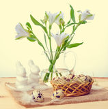 Quail eggs with straw and feathers in basket, white hares on bur Stock Images