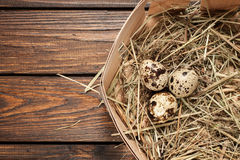 Quail eggs in a straw nest over old wooden background top view Stock Photography
