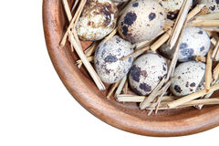 Quail eggs and straw in a wooden bowl isolated on white Royalty Free Stock Images