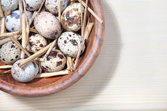 Quail eggs and straw in a wooden bowl on wooden table Royalty Free Stock Images