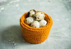 Quail eggs in textile basket on the rustic background Stock Photography