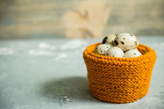 Quail eggs in textile basket on the rustic background Royalty Free Stock Photography