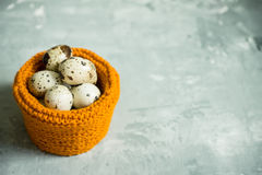 Quail eggs in textile basket on the rustic background Royalty Free Stock Photos