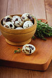 Quail eggs with a thyme. In a wooden cup on a brown kitchen board Royalty Free Stock Image