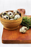 Quail eggs with a thyme in a wooden cup. On a brown kitchen board on a white surface Royalty Free Stock Image