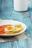 Quail eggs with a toast and tomatoes. Strewed with fresh green onions in a white plate on a wooden turquoise surface Stock Photos