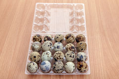 Quail eggs in transparent plastic container on wooden table Royalty Free Stock Images