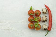 Quail eggs and vegetables at the old cracked shadowed wooden platter. Royalty Free Stock Photo
