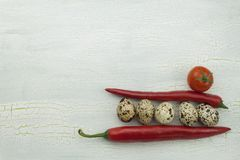 Quail eggs and vegetables at the old cracked shadowed wooden platter. Royalty Free Stock Photos