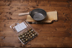 Quail eggs. Vintage wooden trencher and a tray near some quail eggs, wooden background, copy space royalty free stock images