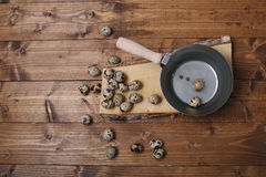 Quail eggs. Vintage wooden trencher and a tray near some quail eggs, wooden background, copy space royalty free stock photography