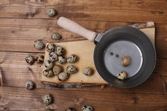 Quail eggs. Vintage wooden trencher and a tray near some quail eggs, wooden background, copy space Stock Images