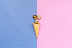 Quail eggs and a waffle cone on blue and pink background. stock photography