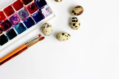 Quail eggs, watercolor paints and brushes on a blue background stock photography