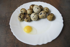 Quail eggs on a white plate. One egg is broken. Quail eggs on a white plate on the brown wooden background. One egg is broken. Healthy eating Royalty Free Stock Photo