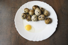 Quail eggs on a white plate. One egg is broken. Quail eggs on a white plate on the brown wooden background. One egg is broken. Healthy eating Royalty Free Stock Image