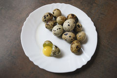 Quail eggs on a white plate. One egg is broken. Quail eggs on a white plate on the brown wooden background. One egg is broken. Healthy eating Stock Photo