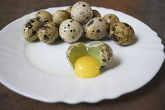 Quail eggs on a white plate. One egg is broken. Quail eggs on a white plate on the brown wooden background. One egg is broken. Healthy eating Stock Image