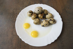 Quail eggs on a white plate. Two eggs is broken. Quail eggs on a white plate on the brown wooden background. Two eggs is broken. Healthy eating Stock Image