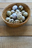 Quail eggs in a wicker basket Stock Images