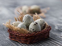 Quail eggs in a wicker basket on a grey wooden background Royalty Free Stock Photography