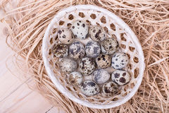 Quail eggs in a wicker basket with straw , top view Stock Photography