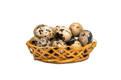Quail eggs in wicker basket on white background royalty free stock photography