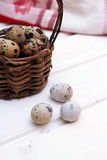 Quail eggs in a wicker basket on a wooden background with kitche Royalty Free Stock Photos
