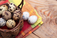 Quail eggs in a wicker basket on a wooden background with napkin Stock Photos