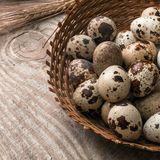 Quail eggs in wicker basket on wooden background stock photography